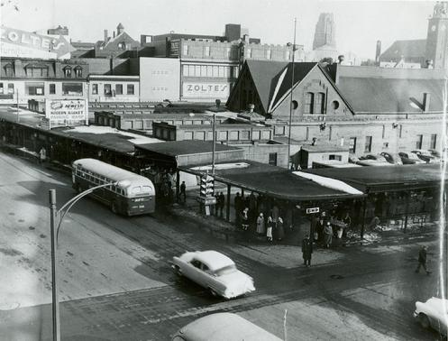 View of the Broadway Market in 1951. Wrap around canopy hosted outdoor market vendors year-round. Lombard Street buildings including Zolte's & Ledermann's Furniture are seen towards the top.